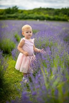 Lächelndes baby im rosafarbenen kleid in einem lavendelfeld tschechien