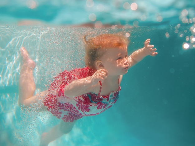 Lächelndes baby in süßem, modernem kleid, das unter wasser im blauen swimmingpool taucht