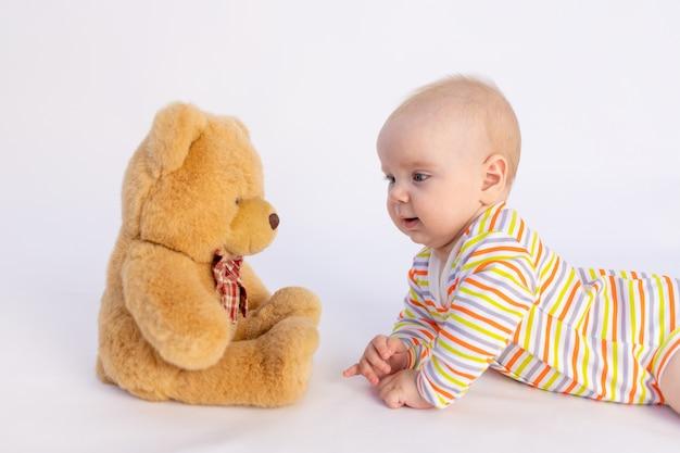 Lächelndes baby liegt auf einem weißen isolierten hintergrund in einem hellen bodysuit vor einem weichen bären