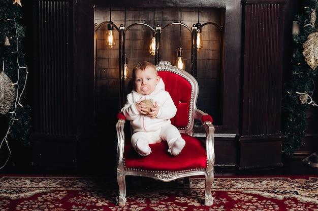 Lächelndes baby unter dem weihnachtsbaum mit 1-jährigen im raum verzierend. kamera betrachten. feier. ferienzeit.