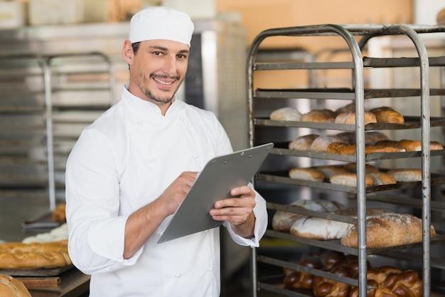 Lächelndes bäckerschreiben im klemmbrett