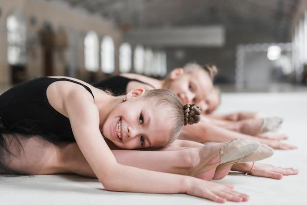 Lächelndes ballerinamädchen, das auf tanzboden mit ihrem freund aufwirft