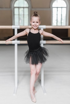 Lächelndes ballerinamädchen im schwarzen ballettröckchen, das vor barre steht