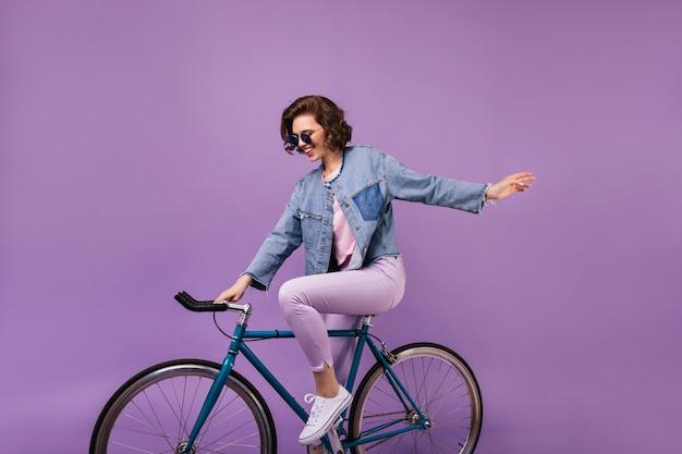 Lächelndes bezauberndes mädchen, das auf blauem fahrrad sitzt. gut gelauntes weibliches model