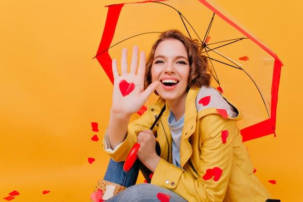 Lächelndes bezauberndes mädchen, das papierherz hält, während unter regenschirm sitzend. innenfoto der dunkelhaarigen frau, die am valentinstag aufwirft.