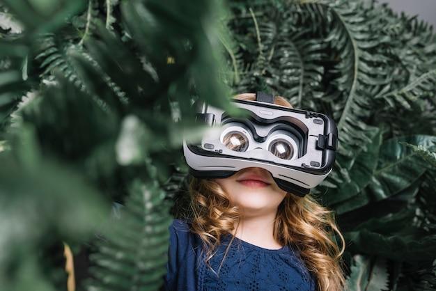 Lächelndes blondes kleines mädchen, das den virtuellen kopfhörer steht unter der grünpflanze verwendet