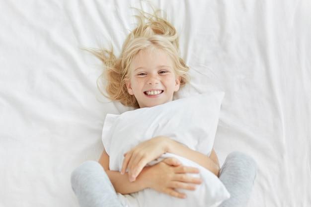 Lächelndes blondes mädchen, das weißes kissen umarmt, während es im kindergarten ist, gute laune hat, während man jemanden sieht und im weißen bett liegt. kleines entzückendes weibliches kind, das schlafenszeit hat. ruhekonzept