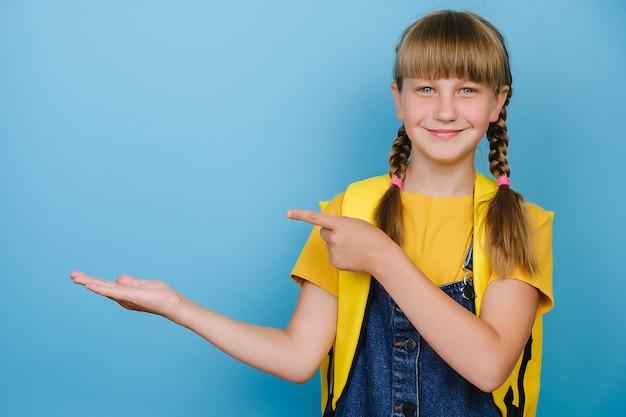 Lächelndes blondes schulmädchen, das auf kopienraum für werbeinhalte zeigt, die hand halten, trägt gelben rucksack und t-shirt und steht isoliert über blauem studiohintergrund. bildung, schulkonzept