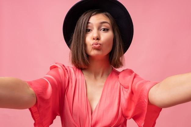 Lächelndes brünettes mädchen, das selbstporträt macht und auf rosa wand aufwirft. sende einen kuss.