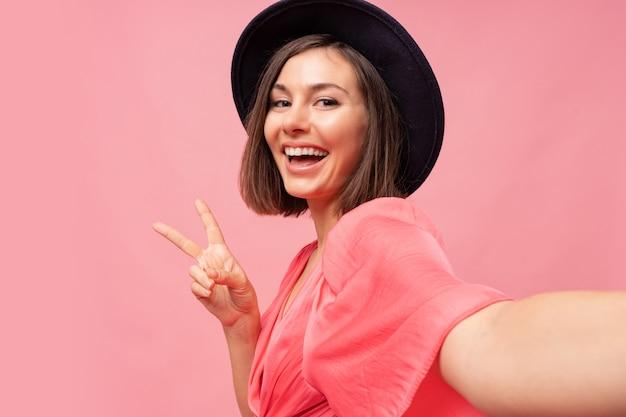 Lächelndes brünettes mädchen, das selbstporträt macht und auf rosa wand aufwirft.