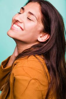 Lächelndes brunettemädchen, das mit mantel aufwirft