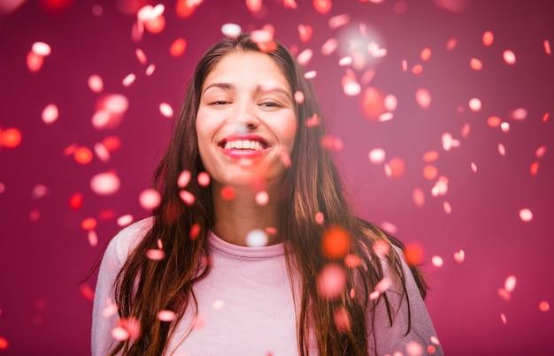 Lächelndes brunettemädchen mit konfetti