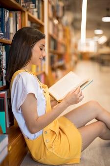 Lächelndes buch der jungen frau lese, das auf boden in der bibliothek sitzt