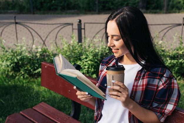 Lächelndes buch der jungen frau lesemit dem halten der wegwerfkaffeetasse beim sitzen auf bank am park