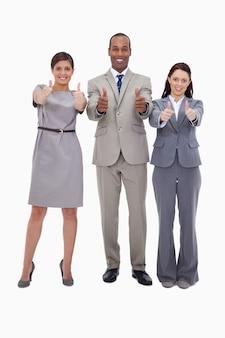 Lächelndes businessteam, das daumen aufgibt