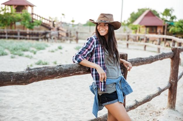 Lächelndes charmantes cowgirl der jungen frau, das auf zaun steht und sich lehnt
