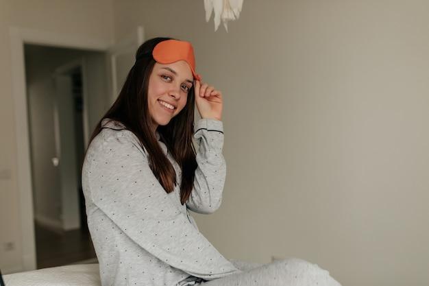 Lächelndes charmantes mädchen, das zu hause in ihrem modernen weißen raum schwach ist und pyjama und schlafmaske trägt, offene augen und fenster betrachtet.