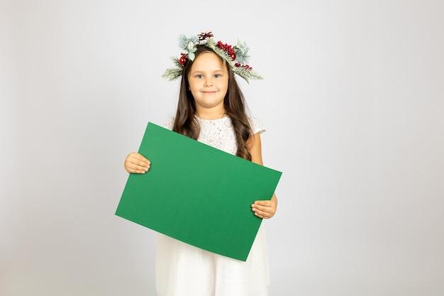 Lächelndes charmantes mädchen im weihnachtskranz hält grüne karte mit leerem raum isoliert auf weißem rücken...