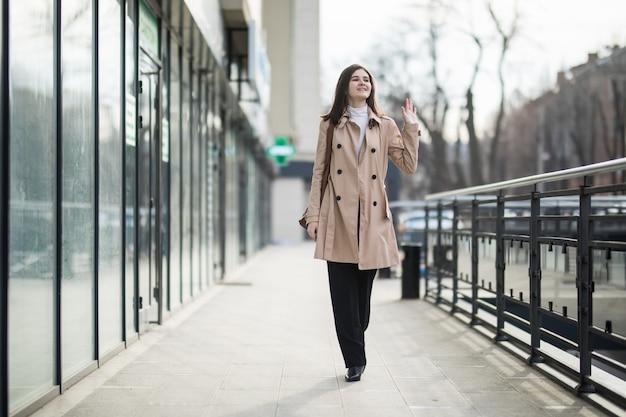Lächelndes damenmodell, das die straße im hellen mantel entlang geht
