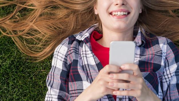 Lächelndes draufsichtmädchen beim halten ihres telefons