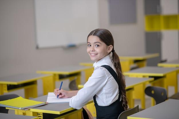 Lächelndes dunkelhaariges schulmädchen, das an ihrem schreibtisch schreibt und im klassenzimmer den kopf zurückdreht