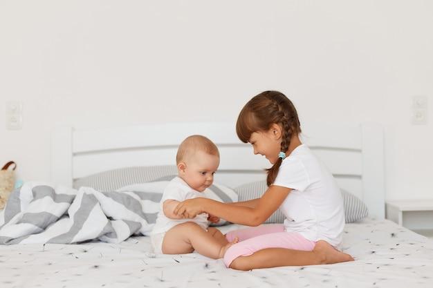 Lächelndes dunkelhaariges weibliches kind mit zöpfen, das legere kleidung trägt und auf dem bett im hellen raum sitzt, kind, das die hände des babys hält, zeit zusammen verbringt.