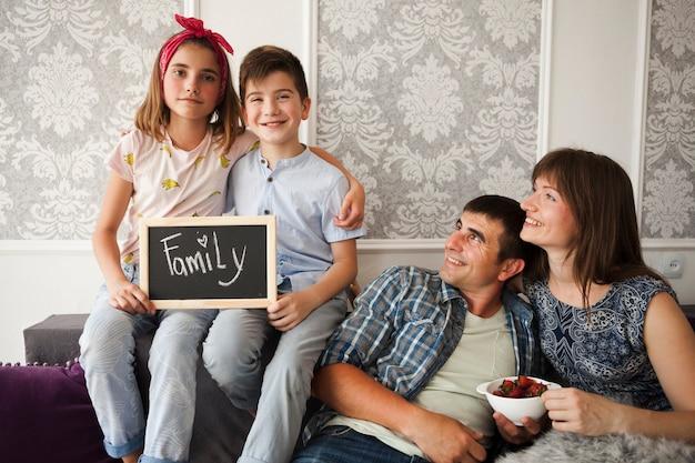 Lächelndes elternteil, das ihre kinder halten schiefer mit familientext betrachtet