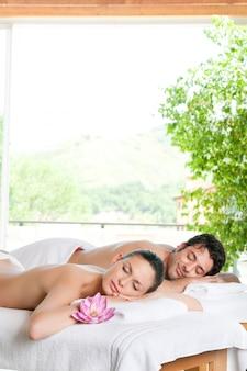 Lächelndes entspanntes paar, das nach einer behandlung im spa zusammen liegt