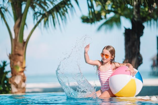 Lächelndes entzückendes mädchen, das mit aufblasbarem spielzeugball swimmingpool im im freien spielt