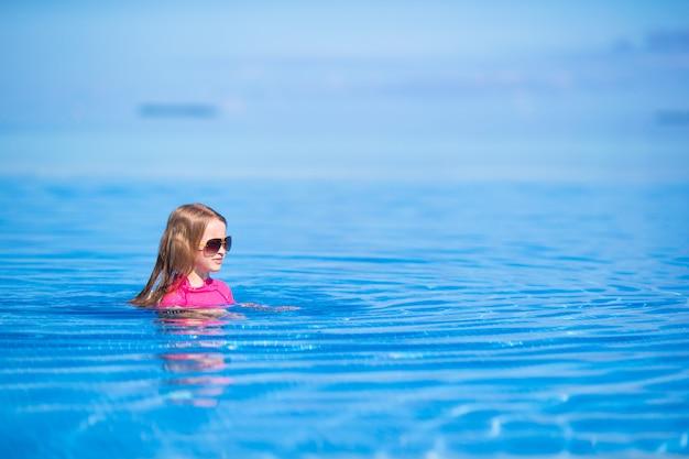 Lächelndes entzückendes mädchen, das spaß swimmingpool im im freien hat