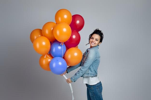Lächelndes entzücktes mädchen im denim, das mit hellen bunten luftballons auf grau lokalisiert aufwirft