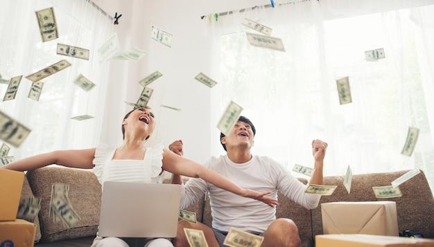 Lächelndes erfolgreiches sitzen des glücklichen paars unter geldregen. online-geschäftskonzept