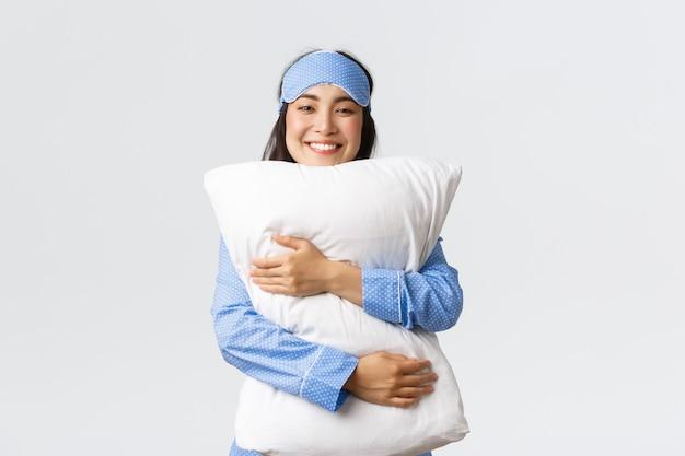 Lächelndes erfreutes asiatisches mädchen in der schlafmaske und im pyjama, die weiches und bequemes kissen mit umarmen