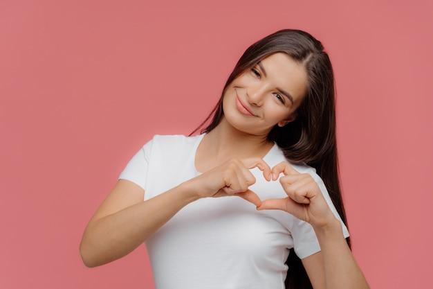 Lächelndes erfreutes weibliches modell des brunette formt herzzeichen