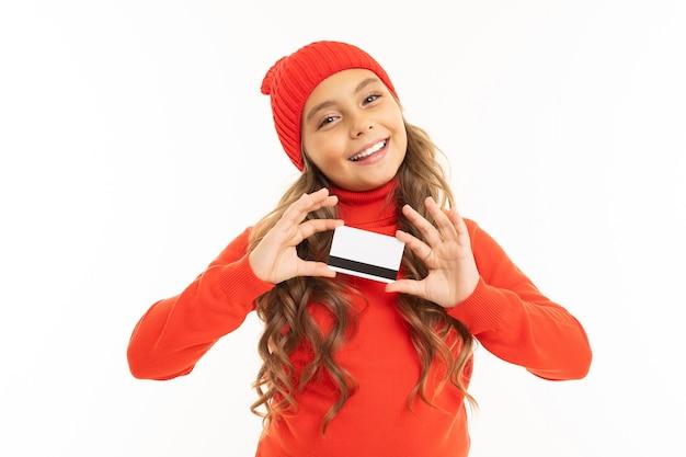 Lächelndes europäisches süßes mädchen, das eine kreditkarte in ihren händen hält