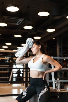 Lächelndes fit mädchen, das handtuch hält und sich im fitnessstudio ausruht. mädchen wischt schweiß mit einem handtuch ab