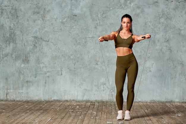 Lächelndes fitnessmodell, das in der turnhalle in voller länge gegen eine graue wand mit jumpern in ihren händen, fitnesskonzept aufwirft