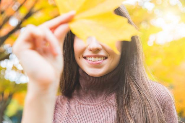 Lächelndes frauenporträt mit einem gelben blatt im herbst