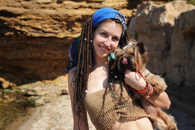 Lächelndes frauenporträt mit ihrem yorkshire terrier hund, mädchen mit dreadlocks