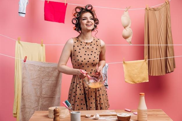 Lächelndes, freudiges mädchen in einem gepunkteten kleid, eier schlagend, auf dem hintergrund eines seils mit kleidern kochend.