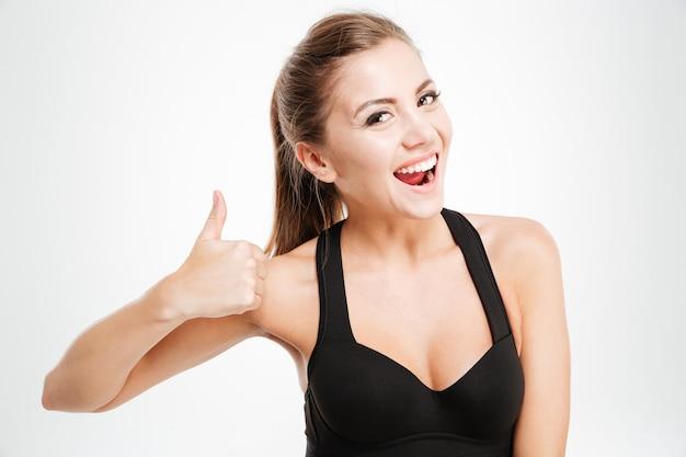 Lächelndes, fröhliches fitness-mädchen in sportkleidung, das daumen nach oben mit einer hand zeigt