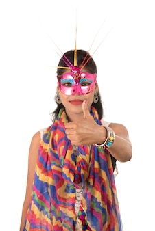Lächelndes fröhliches mädchen, das karnevalsmaske trägt und zeichen lokalisiert auf weißem hintergrund zeigt