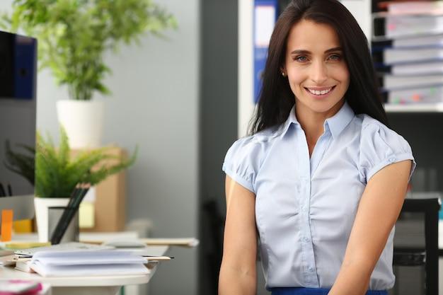 Lächelndes geschäftsfrauporträt sitzen tabelle aganist