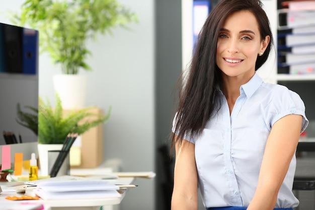Lächelndes geschäftsfrauportrait sitzen tabelle aganist