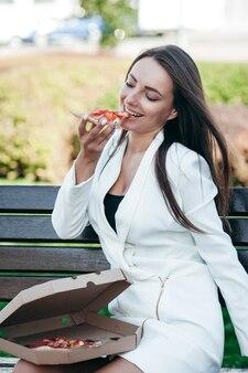 Lächelndes geschäftsmädchen, das pizza an der straße isst