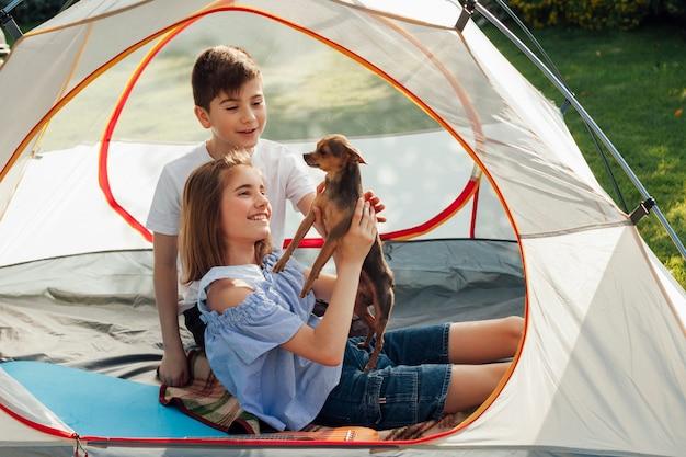 Lächelndes geschwister, das kleinen hund im zelt am picknick streicht