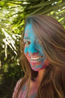 Lächelndes gesicht der jungen frau bedeckt mit der holi farbe, die kamera betrachtet