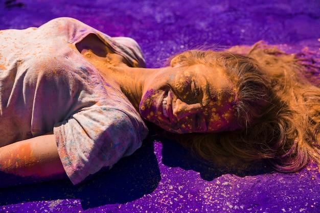 Lächelndes gesicht der jungen frau bedeckt mit holi farbe, die auf purpurrotem pulver liegt