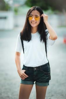 Lächelndes gesicht des asiatischen teenagers, das draußen steht