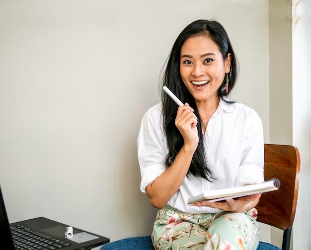 Lächelndes gesicht des reizend schönen freiberuflers mit der kreativen idee, die einen stift und ein anmerkungsbuch hält
